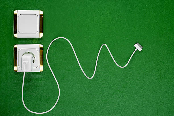 Green charge White charger with its curved cord taken on green wall battery charger stock pictures, royalty-free photos & images