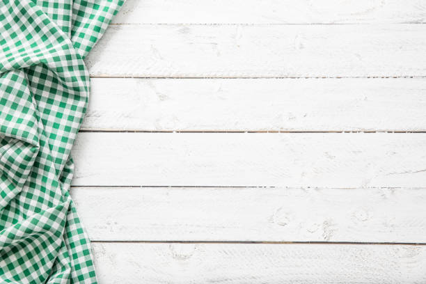 Green checkered kitchen tablecloth on wooden table. stock photo