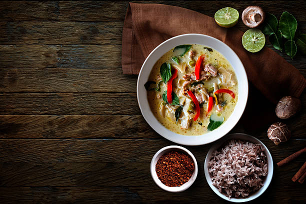 Green Chicken Curry over wooden table.Thai cuisine 스톡 사진