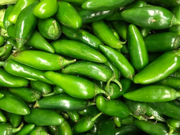 Green chillies A close up of green chilles for sale at a market in Mexico jalapeno pepper stock pictures, royalty-free photos & images