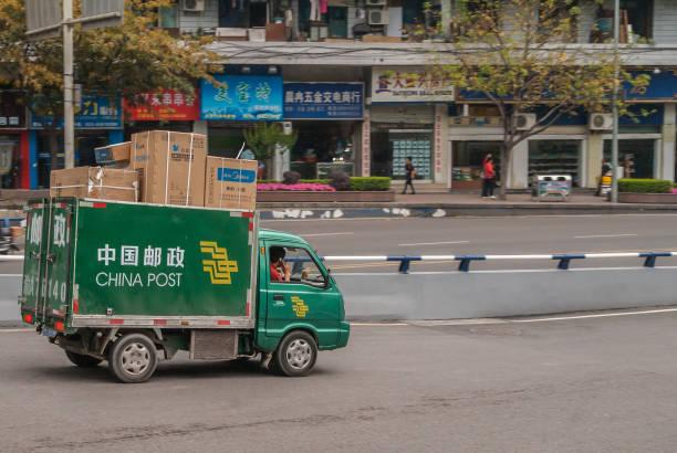 Green China-Post delivery van downtown Chongqing, China. stock photo