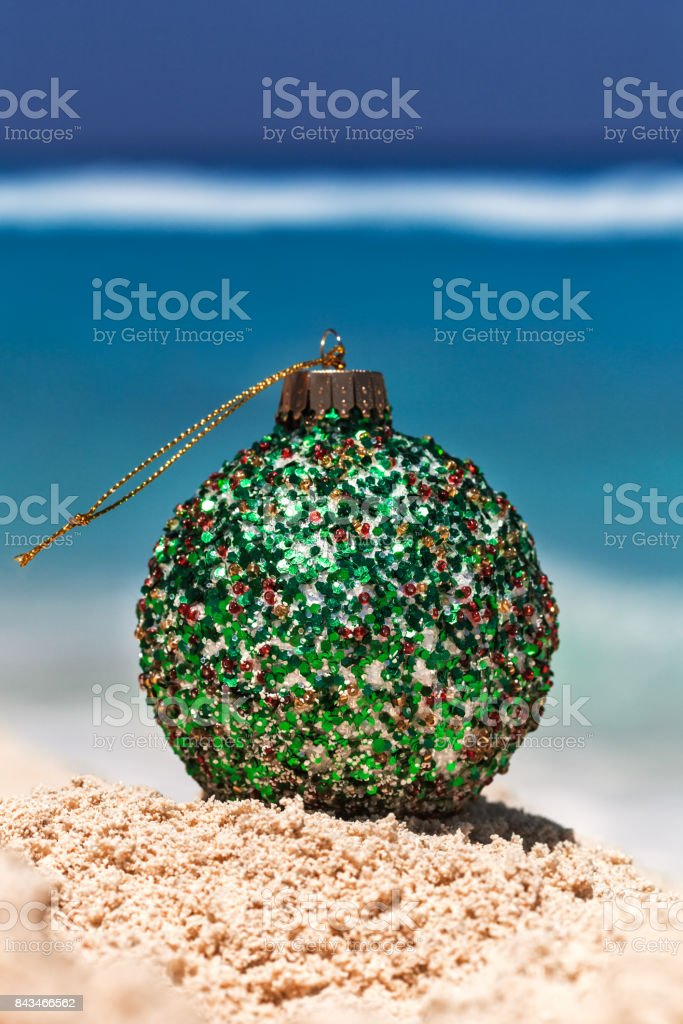 Green Christmas ball on yellow sand at tropical beach, holiday concept stock photo