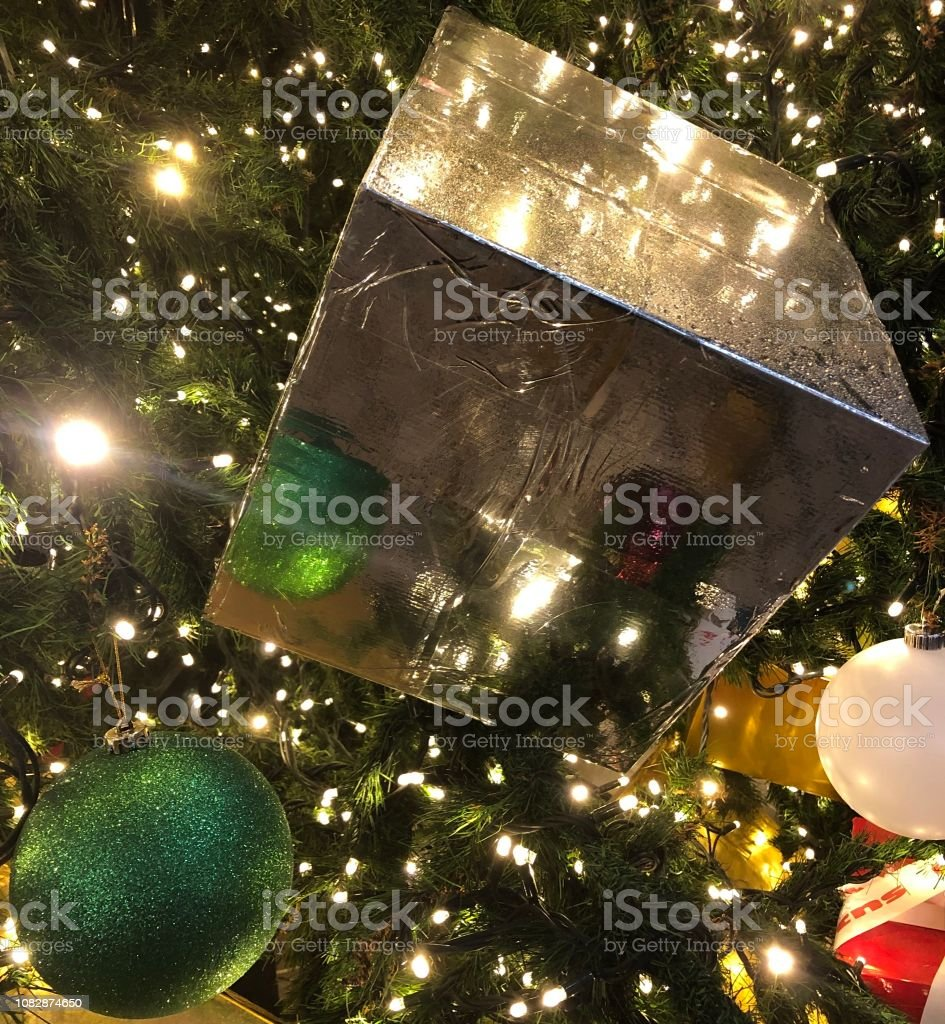 A picture of a green Christmas ball and it's small reflection in a...