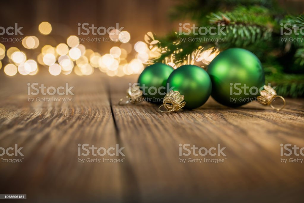 Green christmas balls and fir twigs on rustic wood and sparkles light backgorund stock photo
