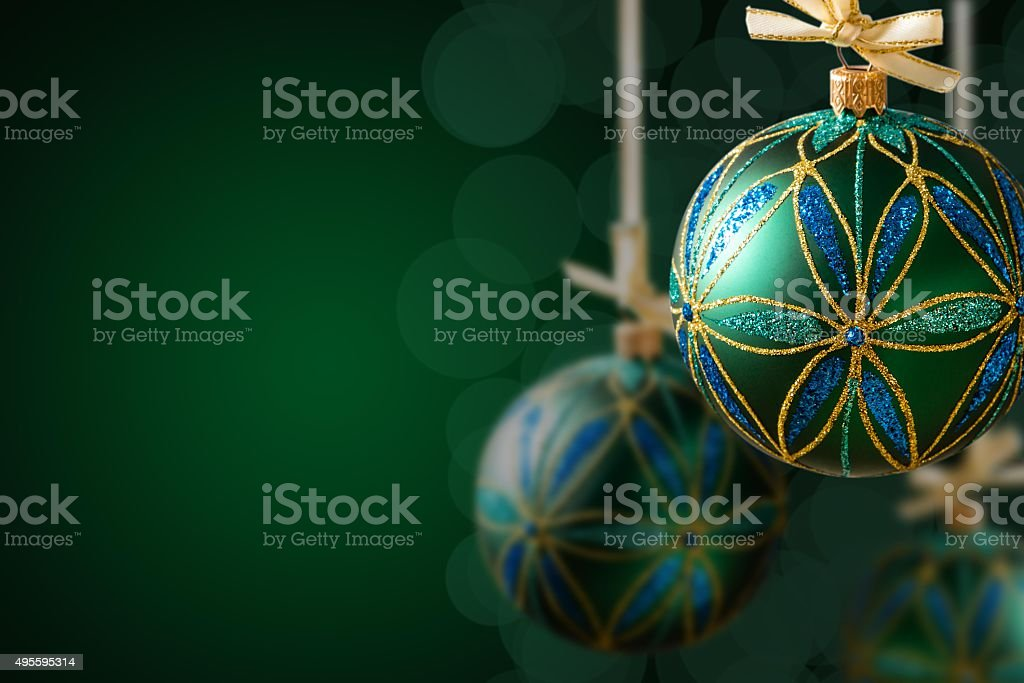 Green christmas balls hanging on abstract background, copy space
