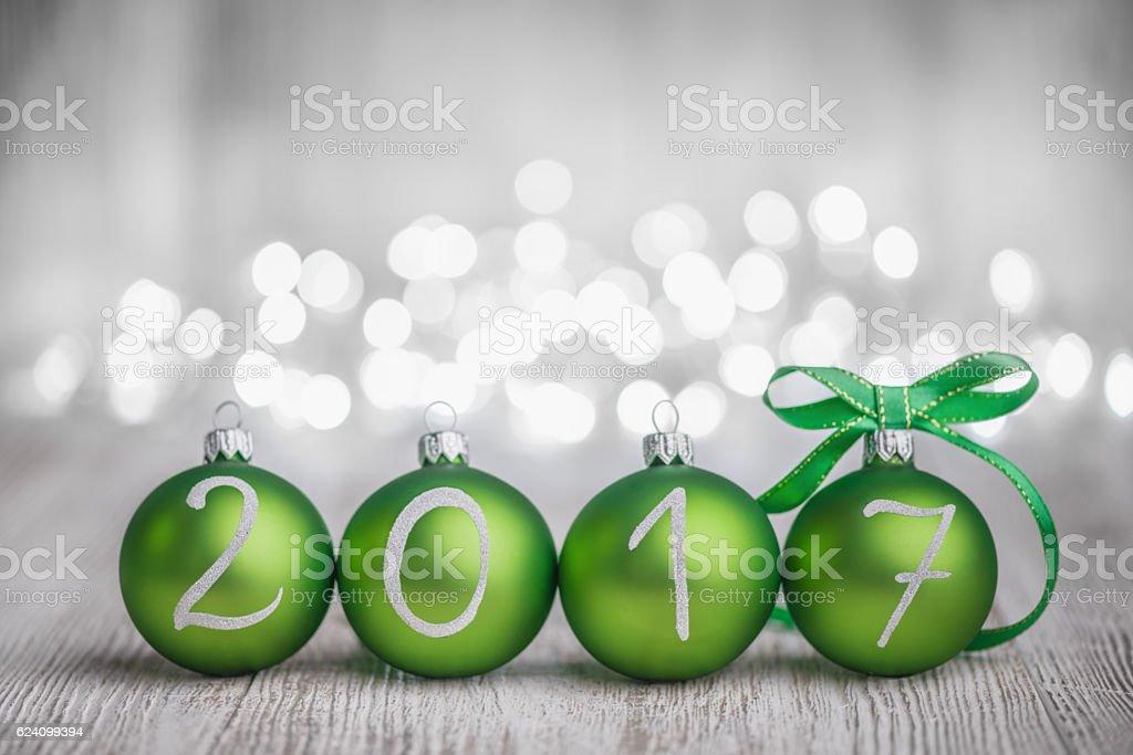 Green Christmas balls on White Rustic Wood Board 2017 year. Defocused...