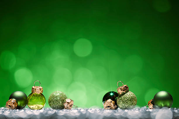 green christmas baubles - glitter bokeh season holiday background - christmas green stock photos and pictures
