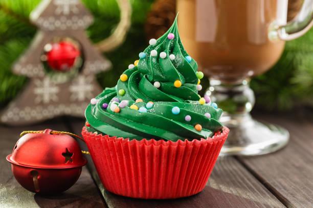 grüne weihnachten-cupcake in rote tasse - heiße schokoladen cupcakes stock-fotos und bilder