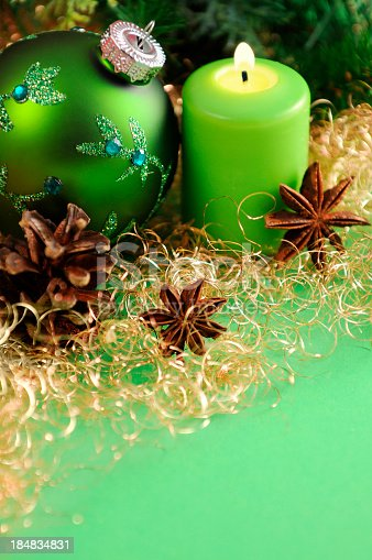 green Christmas ornament and burning candle standing on green paper background. Golden angel hair pasta with star anise. In background green pine twig and cone. Useful Copy space christmas background for greeting card.