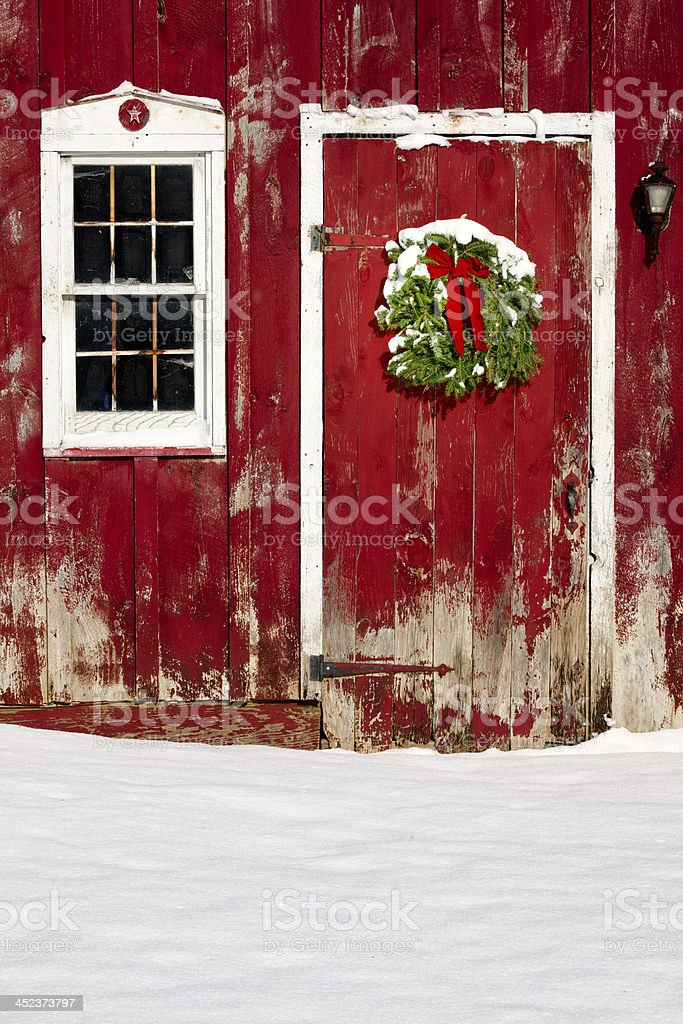 Green Christmas Wreath On Barn Door With Fresh Snow Stock