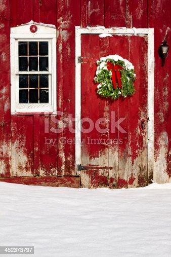 istock Green Christmas Wreath on Barn Door With Fresh Snow 452373797