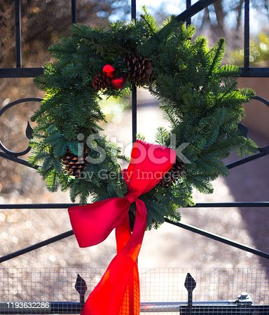 Green Christmas Wreath, Pinecones, Red Bow on Gate. Shot in Santa Fe, NM.