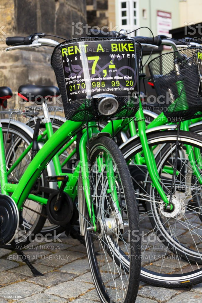 Green city bikes for rent standing on street in Dresden, Germany stock photo