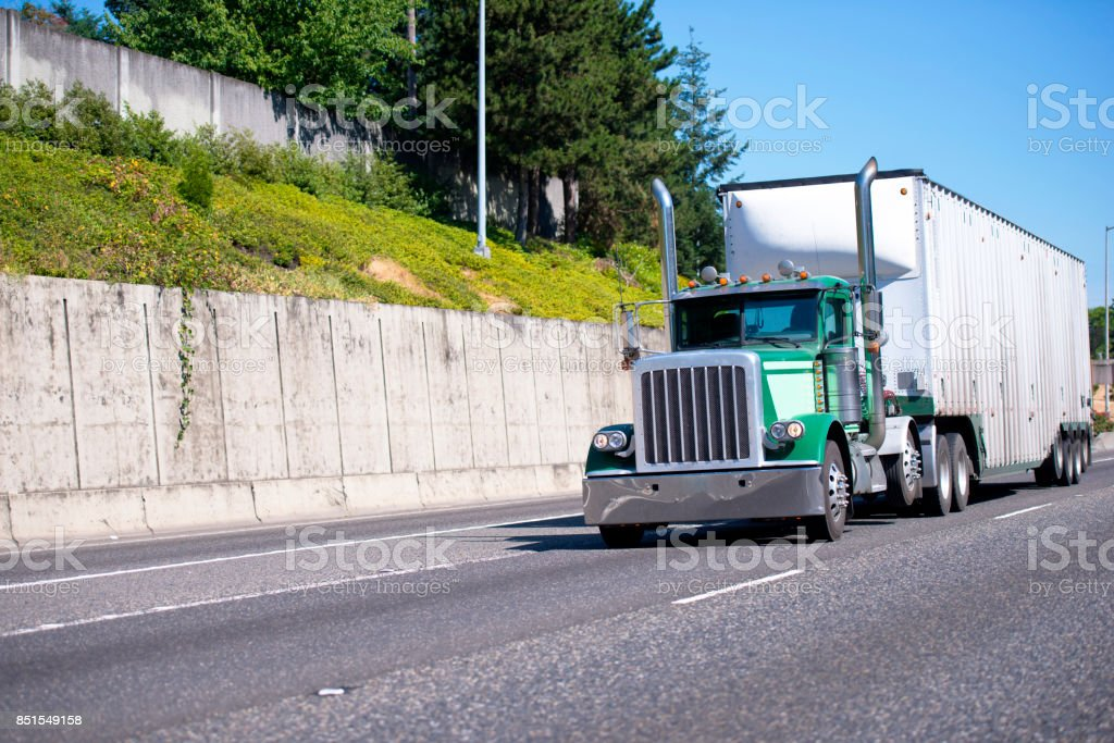 Green classic big rig semi truck with tall pipes and heavy duty bulk trailer transporting cargo on devided highway stock photo