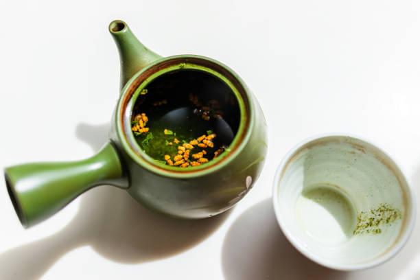 grüner ton teekanne auf weißem hintergrund mit leeren gebrauchten tasse japanischen tee mit kyusu griff brauen genmaicha während der zeremonie offenen deckel mit geröstetem reis - keramikteekannen stock-fotos und bilder