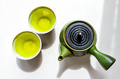 Green clay teapot with kyusu handle flat top flat lay view down on white counter background with Japanese tea brewing genmaicha or sencha in cups during ceremony