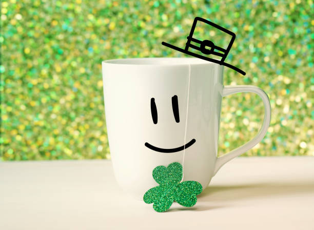 green clover with happy face on white mug - happy st. patricks day stock photos and pictures