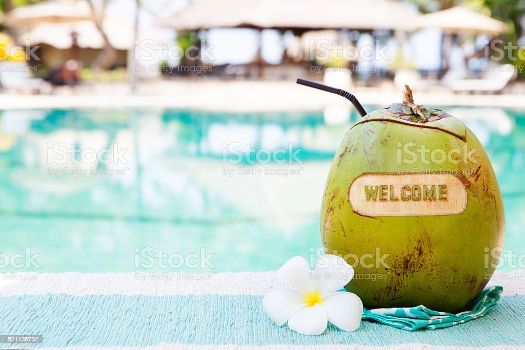 Green coconut with carving welcome on swimming pool summer background stock photo