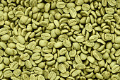 Green coffee beans background. Texture top view.