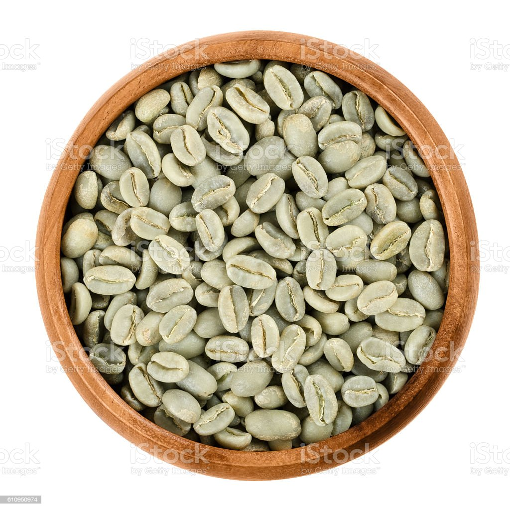 Green coffee beans in a wooden bowl over white stock photo