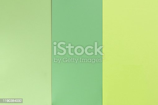Green color paper background, different tints. Geometric flat composition. Empty space on monochrome cardboard