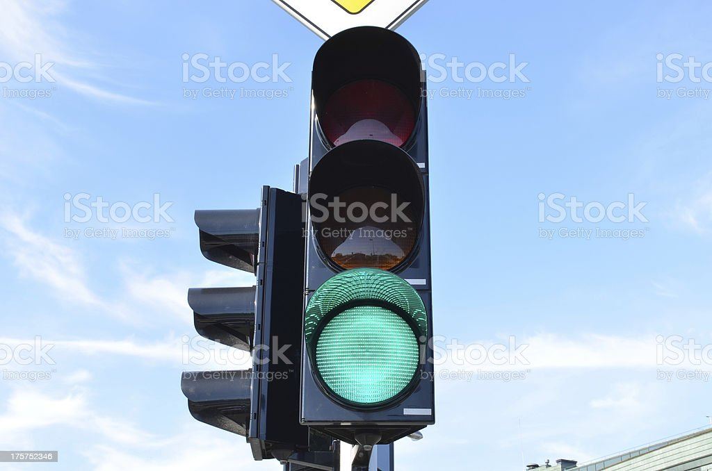 Green color traffic light blue sky in background stock photo