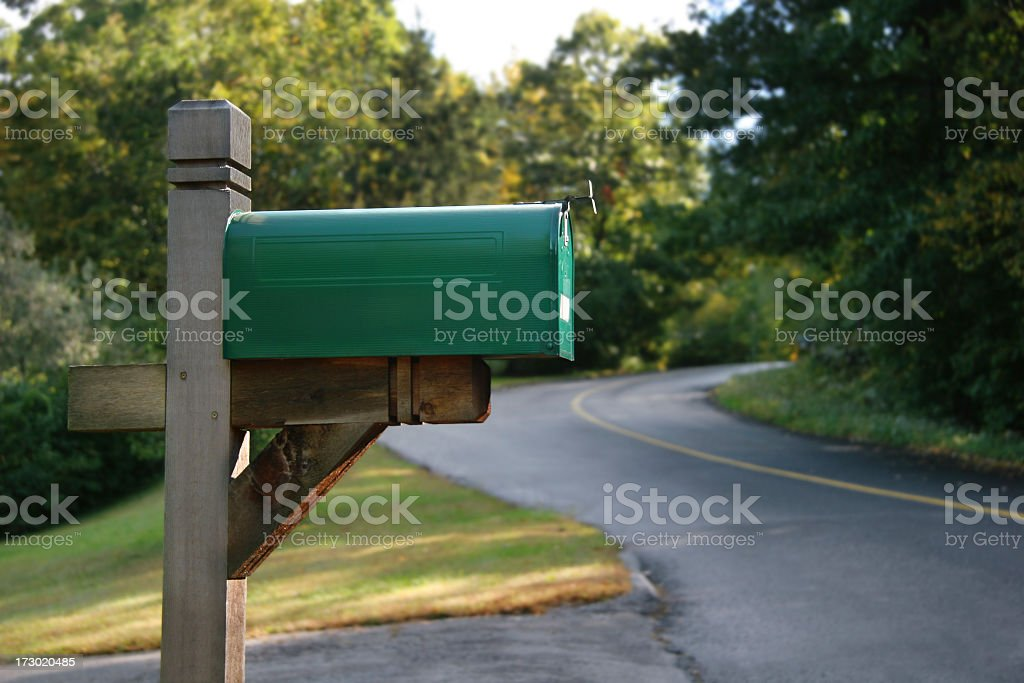 Green colored mailbox, on rural road  stock photo
