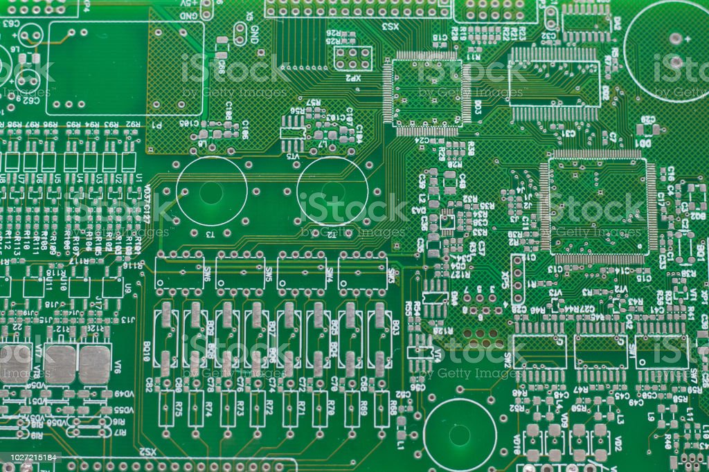 A green computer circuit board background with microcircuits.