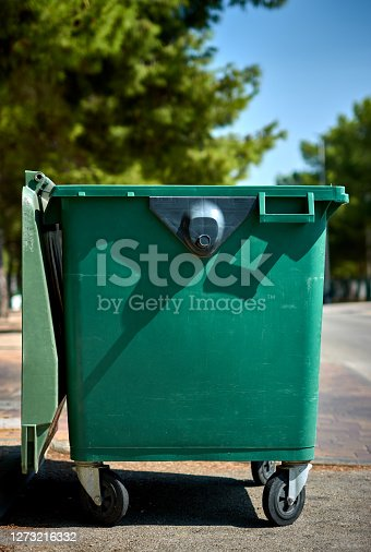detail of an empty green garbage container on the street