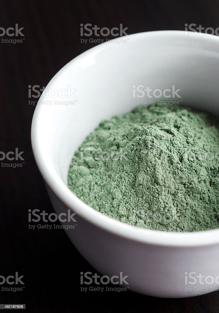 Green cosmetic clay powder in a bowl stock photo