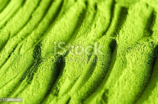 Green cosmetic clay powder (spirulina, algae, seaweed, kelp) texture close up. Abstract background.