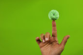 green cotton ball in balance on female finger, concept of leisure of knitting, green background