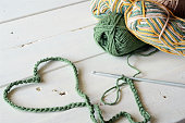 A top view image of a green crochet heart symbol, crochet hook, and crochet yarn.