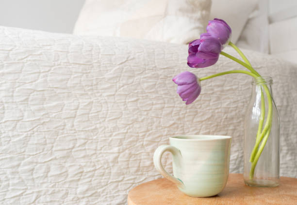 grüne tasse mit violette tulpen neben bett - lila, grün, schlafzimmer stock-fotos und bilder
