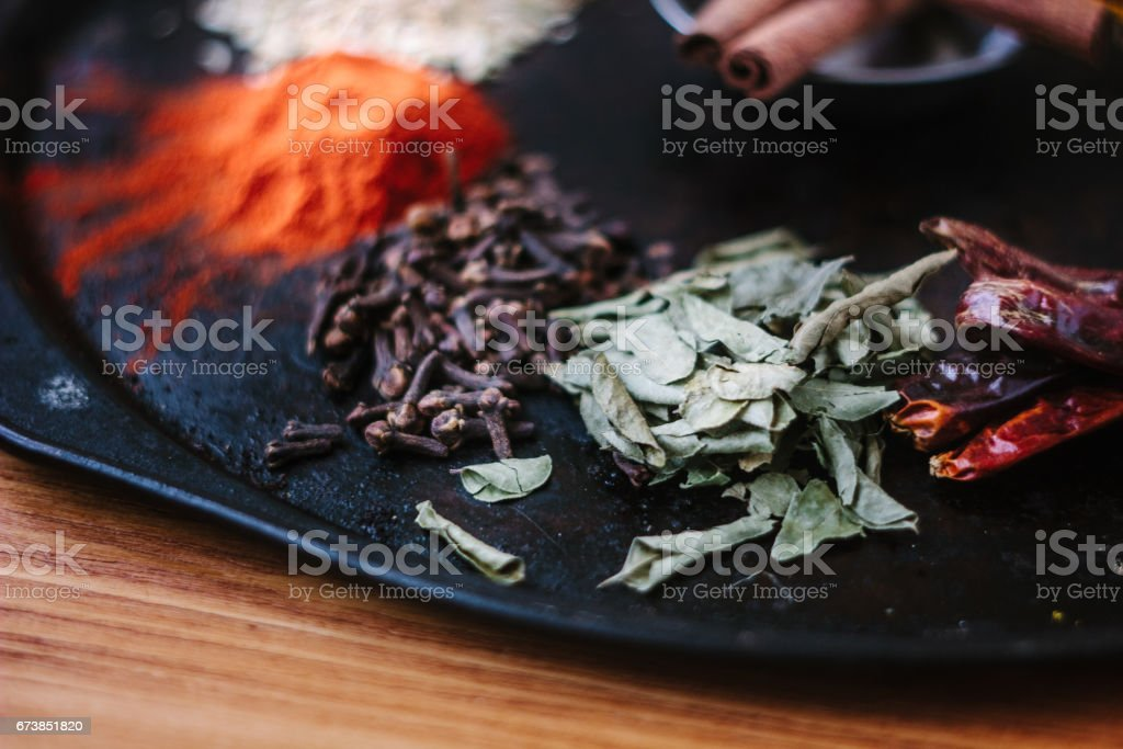 Green curry leaves on black metal plate surrounded by other spices. photo libre de droits