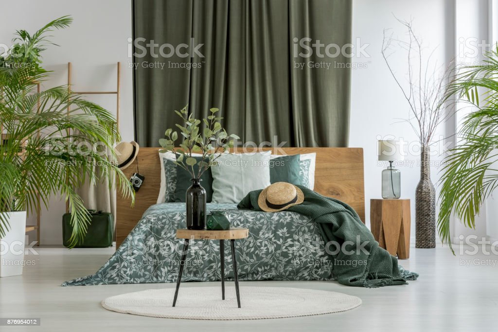 Green curtain behind king-size bed stock photo