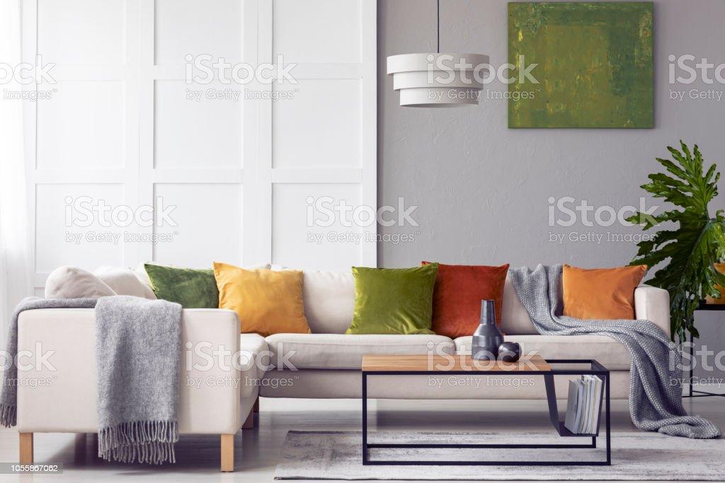 Green Cushions And Grey Blanket On Corner Sofa In Living ...