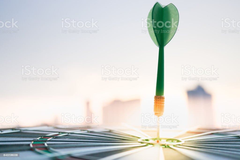 Green dart arrow hitting in the target center of dartboard with modern city and sunset background. Target business, achieve and victory concept . stock photo