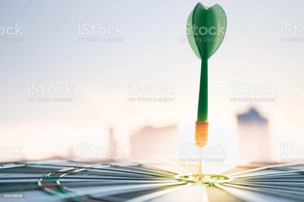 Vert dart flèche frappant dans le centre de la cible de jeu de fléchettes avec la ville moderne et fond coucher de soleil. Cibler les entreprises, à réaliser et le concept de la victoire. - Photo