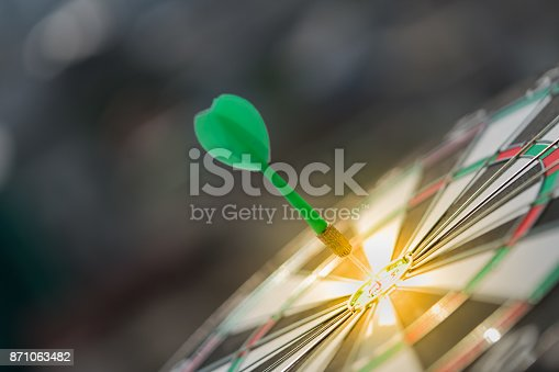 istock Green dart arrow hitting in the target center of dartboard with modern city and sunset background 871063482