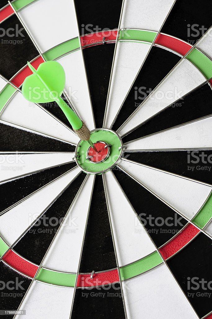 Green dart punctured in the center royalty-free stock photo