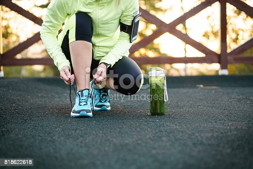 istock Green detox smoothie cup and woman lacing running shoes before workout. 818622618