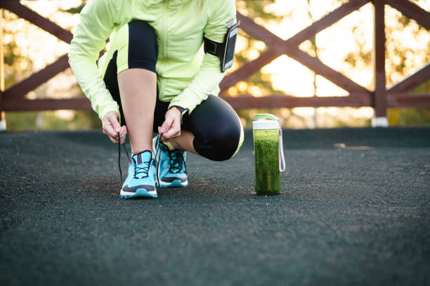 Green detox smoothie cup and woman lacing running shoes before workout. stock photo