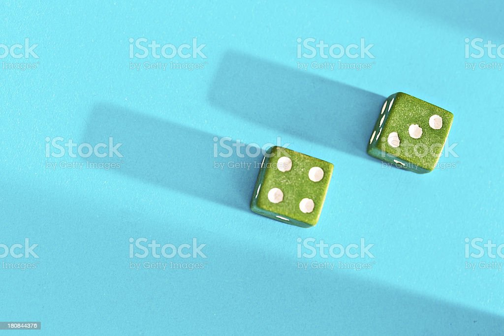 Green dice on blue show 7, lucky for some! royalty-free stock photo