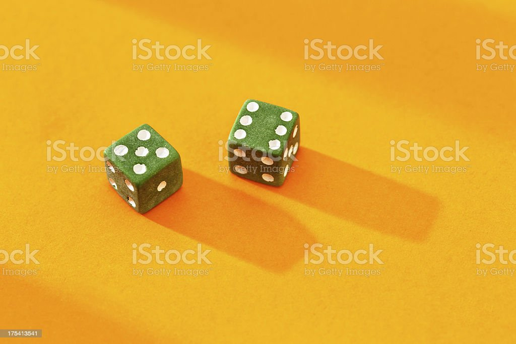 Green dice on golden background show score of 11 royalty-free stock photo