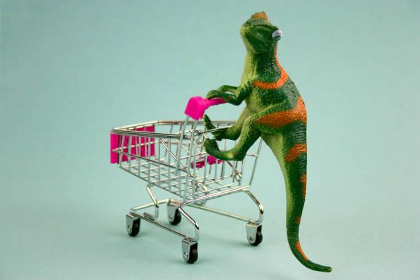 dinossauro verde com carrinho de compras em fundo azul - costumer - fotografias e filmes do acervo