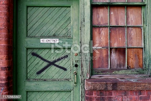 Medium shot of green door and window of abandoned factory