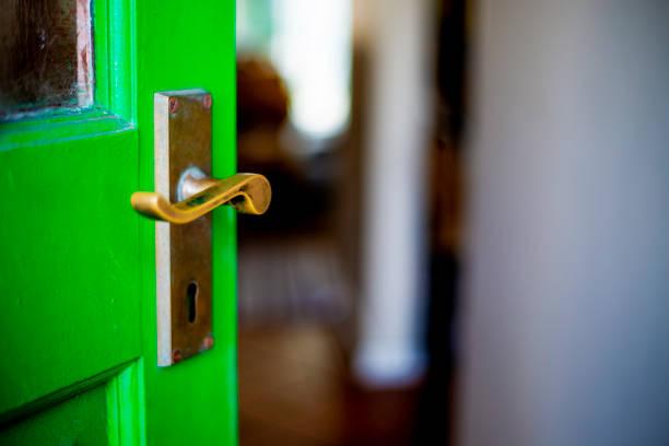 Green door open ajar onto entrance hall stock photo