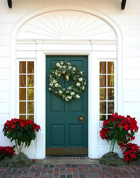 Green door to a white house with a Christmas wreath on it stock photo