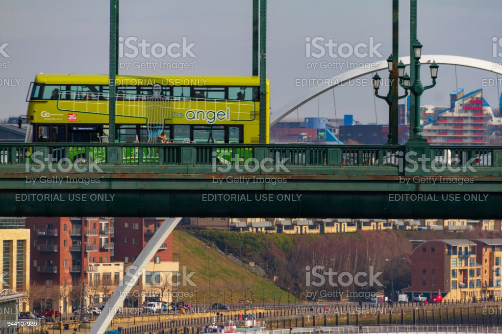 Green double decker bus crossing the Tyne Bridge and Millennium Bridge in the distance at Newcastle Quayside on a cloudy day stock photo